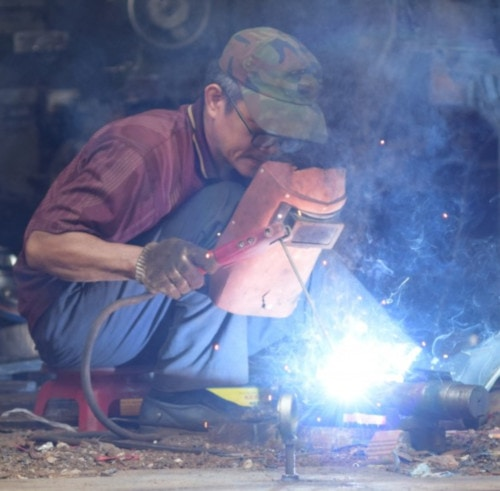 man covering face on welding spark