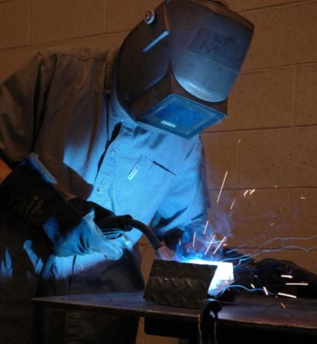 man welding small metal