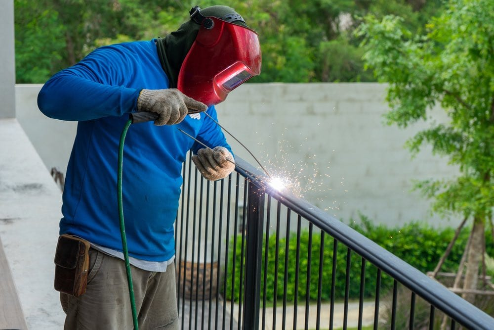 Welding wearing helmet working on fence at home