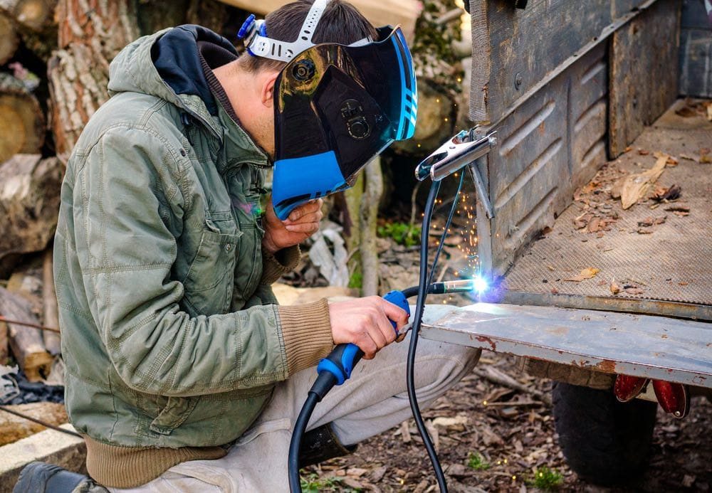 welder performs work at home with a semi-automatic welding machine in a protective mask without gloves.