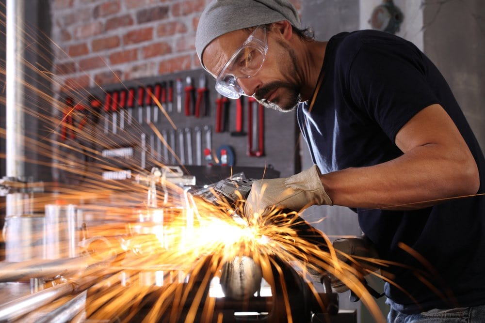 welder working at home workshop with goggles