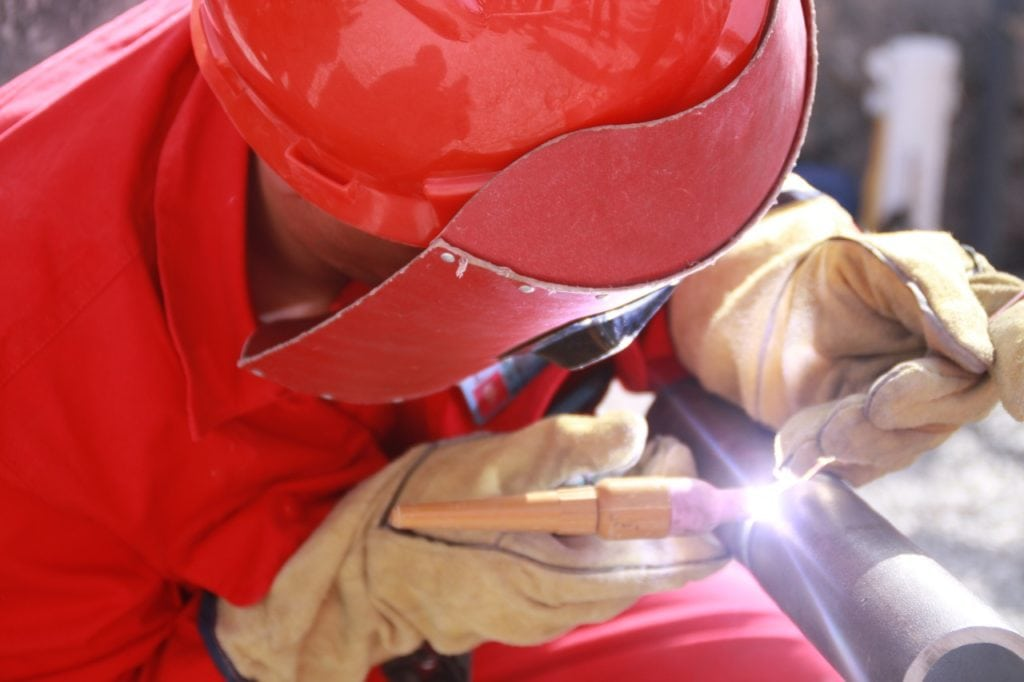 person welding pipe